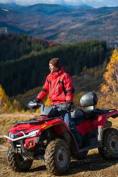Male rider in jacket and hat on a red ATV on mountain roads on a sunny day. Beautiful landscape of forest, mountains and blue sky