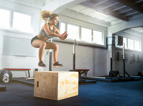 Fitness woman jumping on box training at the gym, crossfit exercise