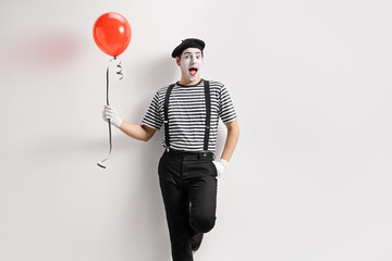 Mime holding a balloon and leaning against wall