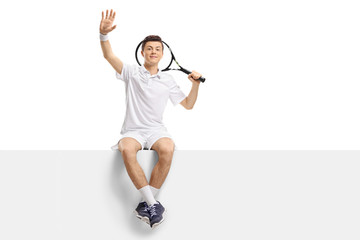 Teenage tennis player sitting on a panel and waving