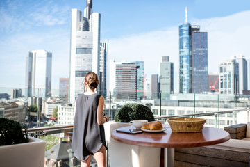 Young businesswoman enjoying great view on the cityscape with skyscrapers in Frankfurt