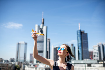 Fototapete - Young woman playing with toy airplane on the modern cityscape background in Frankfurt. Air transportation concept in Frankfurt. Frankfurt has a very large airline connection in Europe