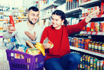 Happy young couple purchasing tinned goods