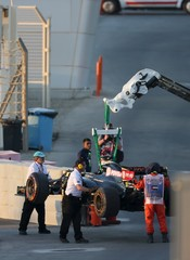Lotus Formula One driver Pastor Maldonado of Venezuela's car is towed after he crashed at the first turn during the Abu Dhabi F1 Grand Prix at the Yas Marina circuit in Abu Dhabi