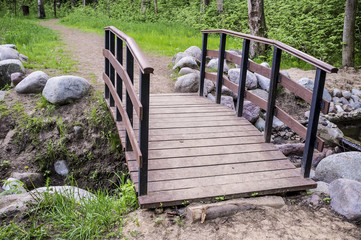 Trail leads to a small wooden bridge over the creek shore is lined with stones, in the summer forest.