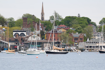Newport Harbor in Newport, Rhode Island. The brown steeple is the historic St. Mary's Church where John F. Kennedy was married. Sailboats and moorings are in the foreground. Seaside, coastal town