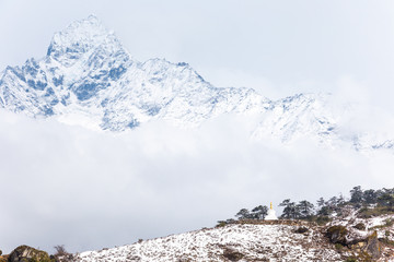 Tiny buddhist stupa and the giant Thamserku mount, 6 623 m, in the background. Himalaya mountains, Everest Base Camp Trek, Sagarmatha National Park, Nepal.