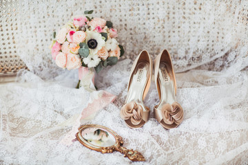 Luxury shoes and bride bouquet on the sofa