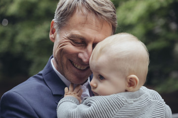 Happy mature businessman holding baby boy outdoors