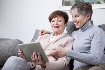 Two senior women sitting on couch, looking at digital tablet
