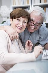 Senior couple embracing and smiling at camera