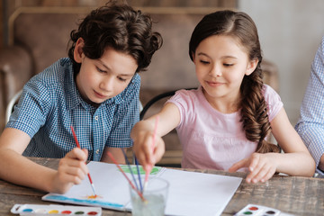 Lovely cheerful kids painting a watercolor picture together