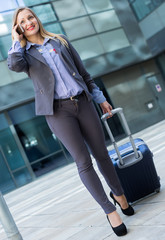 woman in suit standing with baggage and talking phone