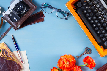 Workspace with orange vintage typewriter, frame with copy space on blue table background