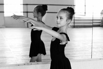 Young and beautiful ballet dancer posing in dance studio. Black and white art photo with bokeh and grain