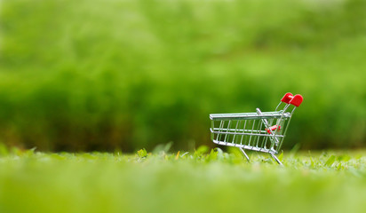 Close up shot of shopping cart over nature green background shallow depth of field