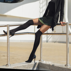 Long slim female legs in knee socks on top of tights and short leather skirt sitting on railing. Street style, urban fashion.