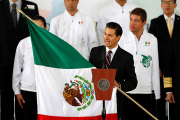 Mexico's President Enrique Pena Nieto holds the Mexico national flag before handing it over to flag-bearer and mountain biker Daniela Campuzano during a ceremony ahead of the Rio 2016 Olympic Games at Los Pinos presidential residence in Mexico City