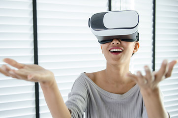 close up woman use virtual reality glasses ( VR ) in her office