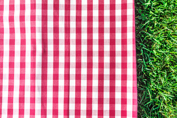 Printed kitchen splashbacks Picnic Red gingham tablecloth on green grass with copyspace