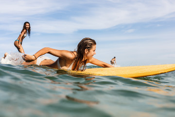 Two beautiful fit surfing girl on surf longboard surfboard board on sunrise or sunset in the ocean. Woman ride good wave while her friend paddle. Modern active sport lifestyle and summer vacation.