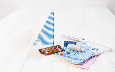 Ship toy and pieces of cloth with sewing accessories