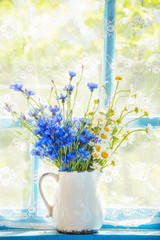 A bouquet of field flowers of cornflowers and chamomiles in a pitcher on the window. Retro, vintage style. Home rural farming situation of the old veranda.
