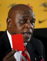 South African businessman and former political prisoner Tokyo Sexwale speaks while holding a red card during a media briefing at SAFA house in Johannesburg
