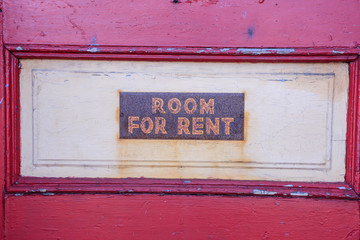 Room For Rent sign on a depalidated dusty door.