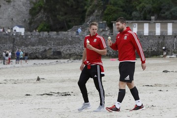 Wales' Edwards and Voke eat icecream as they walk on the beach in Dinard