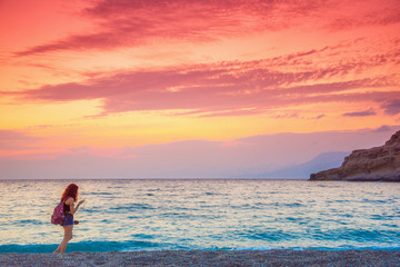Woman walks in beach of matala, at sunset, Crete, Greece
