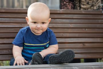 Baby Boy Sitting on Park Bench in Garden