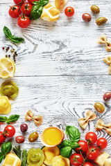 Fresh ingredients for italian lunch or dinner: uncooked tortellini, pasta, raw egg, cheese, tomato, basil and olives, lemon and pepper on white table. Food frame with copy space.