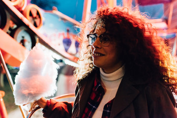 Young beautiful mixed race woman outdoor in a lunapark in the night holding cotton candy - sweet, snack, childhood concept