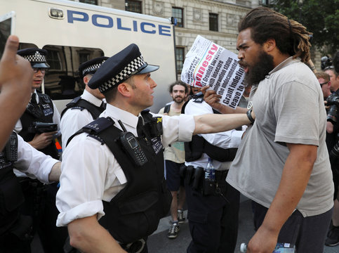 A police officer pushes a demonstrator during a protest in Parliament Square, in central London