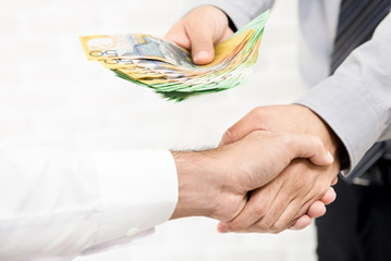 Businessman giving money, Australian dollar banknotes, while making handshake
