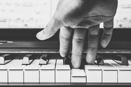 male musician hands playing on piano keys, black and white