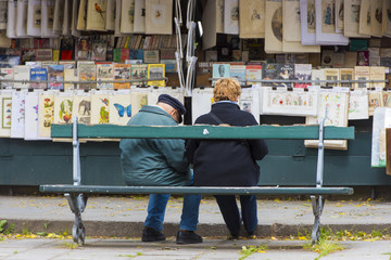 People on a bench at a second-hand book market on quay of river Seine near cathedral Notre Dame in Paris