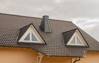 Modernes Ziegeldach mit zwei Spitzgauben mit Dreiecksfenstern in weißem PVC - Modern tiled roof with two vaults with triangular windows made of white PVC