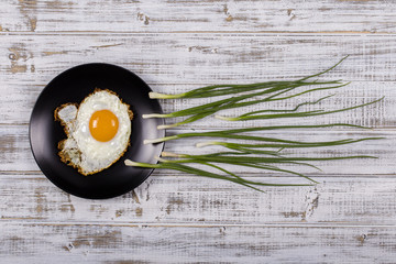 Egg , chives and black plate look like sperm competition, Spermatozoons floating to ovule in white wooden background