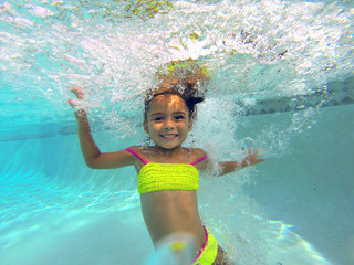 little girl swiming underwater in a pool posing to camera
