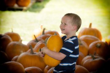 young boy holding pumpkin