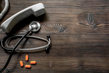 phone handset, pills and phonendoscope on dark wooden desk top view call a doctor space for text