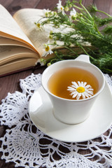 White cup with infusion of tea from daisies and a book in the background on a dark wooden table concept of a healthy herbal vegetable drink and a romantic breakfast
