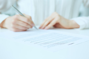 Businesswoman hands sign contract on desk. Female entrepreneur puts signature on official agreement. Profitable deal concept. Business partner accepts conditions. Focus on contract, close up