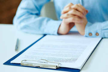 Hands of woman preparing to sign the contract document with pen on desk. selective focus image on sign a contract.