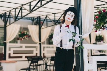 Emotional male mime artist with red rose posing on the summer terrace at the restaurant
