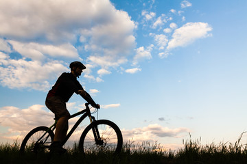 Mountain biker cycling silhouette over blue sky