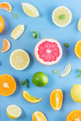 citrus food pattern on blue background - assorted sliced citrus fruits with mint leaves