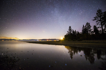 The moon rises over Kiva Beach at night with the night sky reflecting in Lake Tahoe in South Lake Tahoe, California.